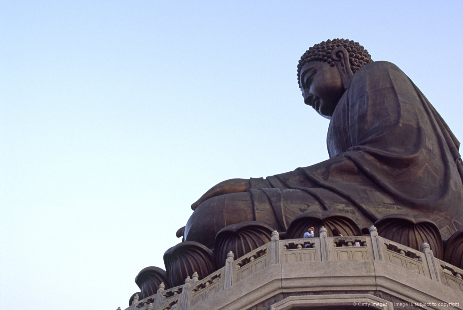 China, Lantau Island, Ngong Ping. A pilgrim is dwarfed by the giant Tian Tan Buddha, a bronze, seated representation of Lord Gautama, sitting above Ngong...