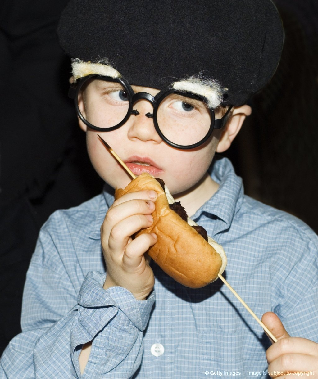 A boy at a masquerade eating.