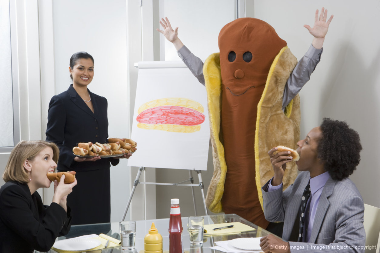 Business people eating hot dogs in conference room with person in hot dog costume